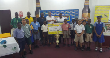 Petra Organization Co-Director Troy Mendonca (centre) collecting the sponsorship cheque valued at $4,000,000 from Courts Managing Director Clyde de Haas in the presence of the several of the students from the participating schools as well as GFF President Wayne Forde (3rd from left), Malta Brand Manager Clayton McKenzie (2nd from left) and Petra Representative Mark Alleyne (left) at the launch of the 5th Annual Courts Pee Wee Boys Football Championship