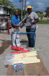 Joel Alleyne, right, of the Malteenoes Cricket Club receives the equipment from Food for the Poor's Wayne Hamilton.