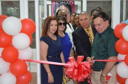 Dr. Shannon Da Silva, BSc (left) and her parents Barbara and Philip Da Silva watch on as Minister of Public Health Dr. George Norton cuts the ribbon to commission the Da Silva's Optical branch in Parika (GINA photo)