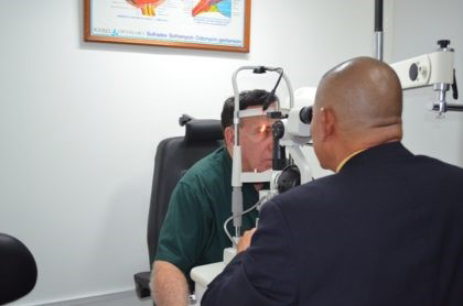 Minister of Public Health, Dr. George Norton performs an Ophthalmology examination on Dr. Philip Da Silva (GINA photo)