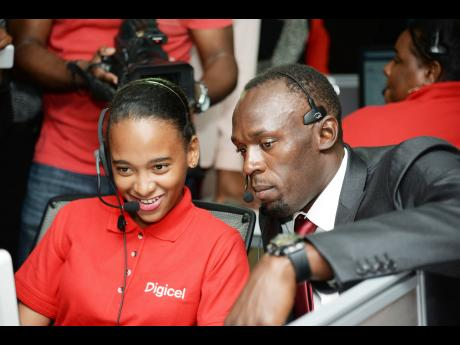 Usain Bolt (right) and Alexia Terrelonge responding to a caller inside the call centre at Digicel during his first day at work at Digicel head office yesterday