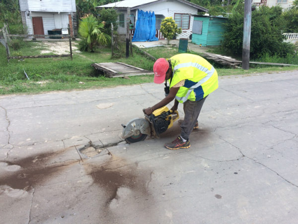 One of the workers cutting around one of the potholes in the road.