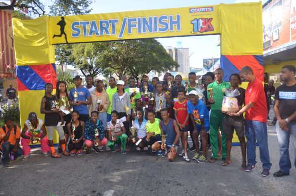The top prize takers pose for a photo in front of Courts on Main Street following the sixth annual 10K and Fitness Run.