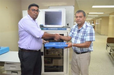 Surgeon and Senior Surgical Registrar, Dr. Ravi Motilall (left) hands over endoscopic equipment to Chief Executive Officer of the Georgetown Public Hospital Corporation, Michael Khan (GINA photo)