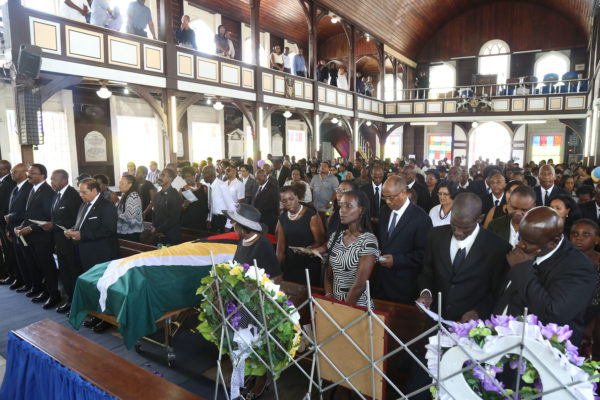 Justice Winston Moore's widow, Vera Moore, glances over at the casket bearing her late husband's remains during his funeral service at St Andrew's Kirk yesterday. Standing next to her are three of her children. Also in picture (from second left) are Attorney-General Basil Williams, Speaker of the National Assembly Dr. Scotland Barton and acting President Moses Nagamootoo. (Keno George photo).