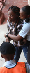 A police officer attempts to escort Rushelle Gittens out of the court compound