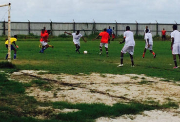 Daniel Floy (centre) of Uitvlugt Secondary in the process of unleashing a powerful goal bound strike during his team's win over Vreed-en-Hoop Secondary in the Secondary School final of the Ministry of Social Protection West Demerara football championships Saturday.