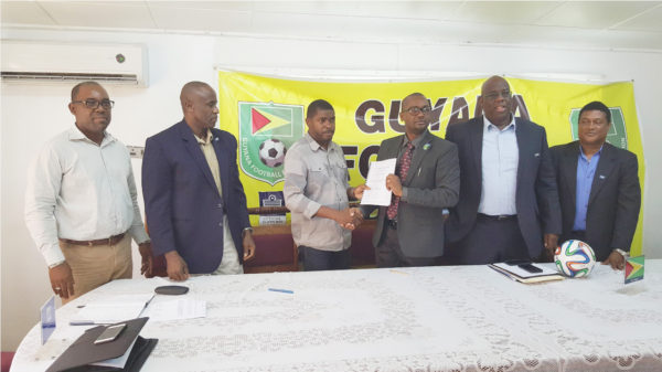 GFF President Wayne Forde (3rdfrom right) handing over the signed contract to Dwain Ferdinand of Home Designs and Engineering Associates while FIFA Development Officers Howard McIntosh (2ndfrom right) and Anton Cornel (right) alongside GFF Vice Presidents Rawlston Adams (left) and Bruce Lovell (2ndfrom left) look on
