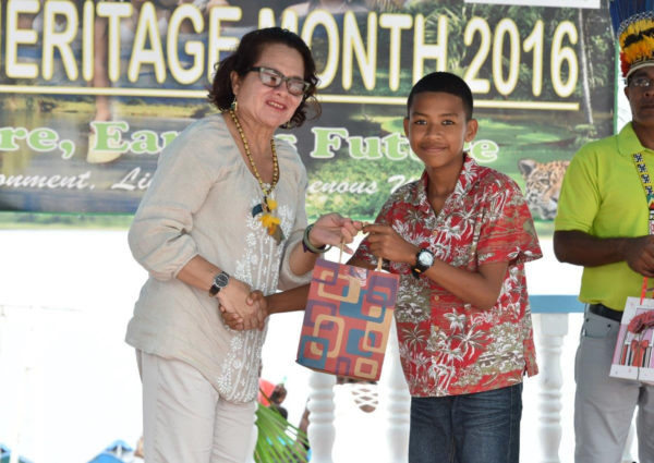 First Lady Sandra Granger making a presentation to Roland Chesney, a student, who performed outstandingly at the National Grade Six Assessment. (Ministry of the Presidency photo)