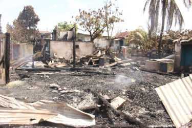 The charred remnants of Lot 50 McDoom, where the fire reportedly began before spreading to other homes. (Photo by Keno George)