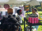 Jasmine Farley (red flowers in hair) answers the questions of a potential customer visiting her booth during the Exhibition