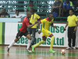 Nyk Nichols (28) of Guyana trying to launch an attack while being pursued by a Surinamese player during their matchup at the Cliff Anderson Sports Hall in the Inter-Guiana Games Futsal encounter yesterday. (Orlando Charles photo)