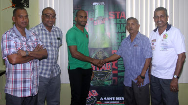 Lindon Henry of Stag Beer  shake hands with GFSCA President Ramchand Ragbeer at yesterday's sponsorship ceremony. (Orlando Charles photo)
