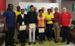 The recipients of the Courts university scholarships, standing with Representatives of Courts Guyana Inc.