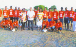 UK based Guyanese Anthony Price (centre) posing with members of the Trafalgar United FC, inclusive of Club Coordinator Yvette Price, after a simple presentation of football kits and equipment at the No. #30 Ground in West Coast of Berbice. The presentation was done on behalf of Pastey Farr of Sainsbury's Supermarket in Winchester, England.