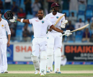 Batsman Darren Bravo celebrates his eighth Test hundred yesterday as captain Jason Holder (right) applauds the occasion. (Photo courtesy WICB Media) See page 26
