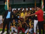 Guyana Coach Levi Nedd (center) and his victorious boys team share a photo with Director of Sports Christopher Jones (left).
