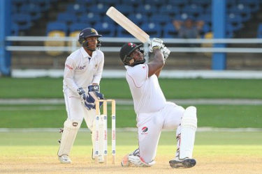 Wicketkeeper Mario Rampersad watches as Roshon Primus clears the ropes for one of his five sixes during his top score of 65 for T&T Red Force on Saturday. (Photo courtesy WICB Media)
