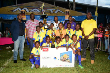 St. Angela's captain Antwoine Vincent (3rd from left) displaying the championship trophy alongside his teammates following their hard-fought win over St. Agnes in the Courts Pee Wee Football final while GFF President Wayne Forde (left), Courts Financial Controller  Neil Boucher (2nd from left), Head-Coach Oscar Payne (centre), Courts Marketing Director Pernel Cummings (2nd from right) and Banks DIH Limited Malta Brand Manager Clayton McKenzie (right) look on