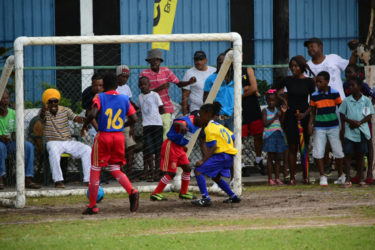Seon Cato (right/yellow) scoring the decisive goal against fierce rival St. Agnes to seal the championship in the 5th Annual Courts Pee Wee Championship at the Thirst Park ground