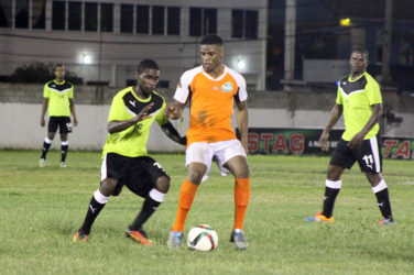 Eon Alleyne (centre) of Fruta Conquerors bracing himself for the impending challenge from a Topp XX player during their matchup in the GFF Stag Beer Elite League Season II opening night at the DCC ground
