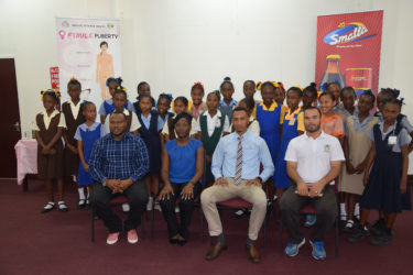 Students from the participating primary schools are all smiles at the launch of the 3rd Annual Smalta Girls Pee Wee Football Championship, in the presence of (sitting from left to right) Petra Organization Co-Director Troy Mendonca, Joy Gravesande, Health Officer of the Ministry of Public Health, Smalta Representative Sean Abel, and Nicholas Fraser, Head of Physical Education Department of the Ministry of Education