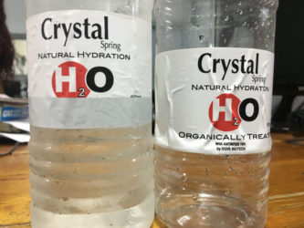 The bottle of water on the left covered with the grey strip.  At right, the hidden labelling is revealed once the strip was removed.