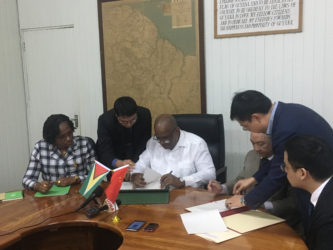 Minister of Finance Winston Jordan (third from left) signing the agreement yesterday with Chinese Ambassador to Guyana Zhang Limin (third from right). Looking on are Minister within the Ministry of Public Infrastructure Annette Ferguson (left) and Chinese and local officials.