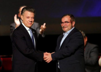 Colombia's President Juan Manuel Santos and Marxist FARC rebel leader Rodrigo Londono, known as Timochenko, shake hands after signing a peace accord in Bogota, Colombia November 24, 2016. REUTERS/Jaime Saldarriaga
