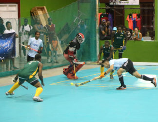 Hat-Trick Sealed- Queens Park hitman Jordan Vieira (right) blasting into the net after skipping past hikers custodian Jason Hoyte (centre) to give his side a 5-4 lead in their Men's Division matchup at the National Gymnasium.