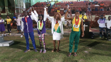 Ira Lewis, popularly known as 'Lady Ira' raises the hands of some of the athletes who received racing watches following last night's National Schools Cycling, Swimming and Track and Field Championships.
