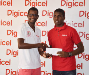 Fruta Conquerors talisman Jeremy Garrett (right) accepting the ticket from Digicel Customer Care executive Sherwin Osbourne for his training stint at European giant Sporting Lisbon of Portugal.