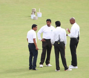 BANGING HEADS: Match officials mull over the state of play during the rain-affected contest at Queen's Park Oval. (Photo courtesy WICB Media)
