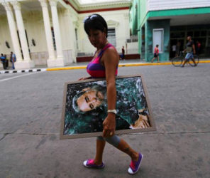 A woman carries a portrait of Cuba's late President Fidel Castro in Santa Clara, Cuba, November 30, 2016. REUTERS/Ivan Alvarado