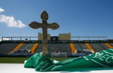 A cross is pictured over a flag of Chapecoense soccer club atop an altar prepared to a mass in tribute to their players at the Arena Conda stadium in Chapeco, Brazil November 30, 2016. REUTERS/Ricardo Moraes