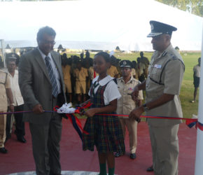 Minister of Public Security, Khemraj Ramjattan (left), Commissioner of Police, Seelall Persaud (right) and Sade Jones, a student of the Green Acres Primary School during the cutting of the ribbon.
