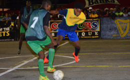 Devon Johnson (right) of Broad Street Bullies battling with a Howes Street player for possession of the ball during his team's 3-0 victory at the Demerara Park in the Guinness 'Greatest of the Streets' Georgetown Zone. (Orlando Charles photo)