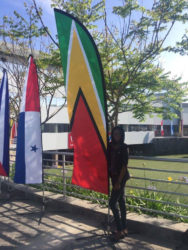 Abbigale standing pruoudly beside a Guyana flag located outside a university in Peru.