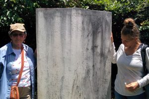 Laura Johnston Kohl (left)  and Jordan Vilchez at the tombstone in Jonestown that was built in honour of the victims