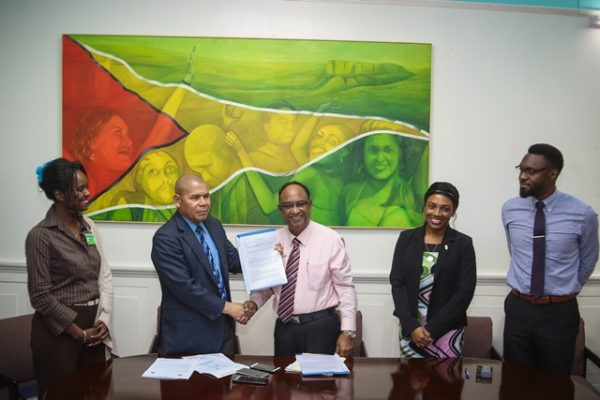 Minister of Social Cohesion, Dr. George Norton (second from left) receiving the agreement from Guyana Amazon Warriors Operation Manager, Omar Khan. (DPI photo)