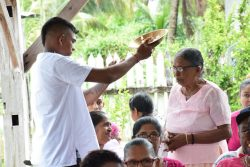 Ramesh Sancharra's eldest son paying respects to an elder. (DPI photo)
