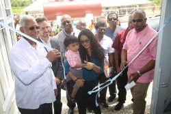 Minister of Agriculture Noel Holder (at left) along with other officials helps to cut the ribbon on the newly-commissioned Enmore drainage pump station. (Terrence Thompson photo)