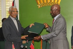 President David Granger (left) and Trinidadian Prime Minister Dr Keith Rowley exchanging copies of the MoU yesterday at State House.