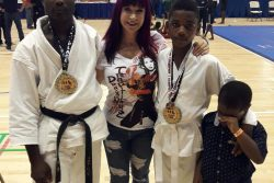 Sensi Troy Bobb (left) and Niquann Fevrier (third from left) with the famous movie star and grand master in Martial Arts, Cynthia Rothrock after their victory.