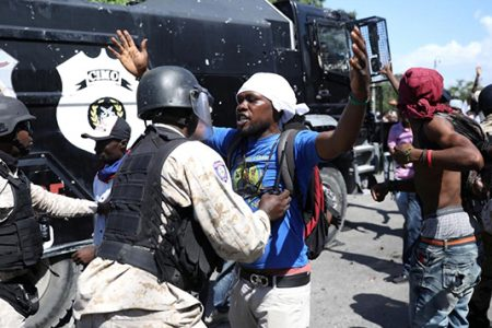 A Haitian National Police officer pushes a protester during a march to demand an investigation into what they say is the alleged misuse of Venezuela-sponsored PetroCaribe funds, in Port-au-Prince. REUTERS/Andres Martinez Casares