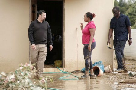 A Greenvale Garden, La Horquetta resident who was affected by floods complains to National Security Minister Stuart Young (left)