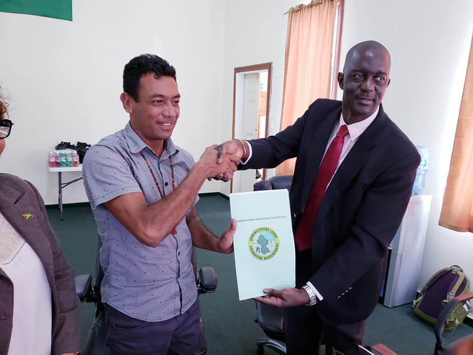Chairman of the NTC Nicholas Fredericks (at left) receiving the lease from Commissioner of the GL&SC Trevor Benn (GL&SC photo)
