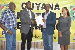 GFF President Wayne Forde (2nd right) presenting the Disciplinary Code to GFF Disciplinary Committee Chairman Roger Yearwood in the presence of two other committee members.