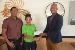 GFF representative Lakeisha Pearson (centre), receiving the sponsor's cheque from German Restaurant Proprietor Clinton Urling. Also in the photo is Kashif and Shanghai Co-Director Kashif Muhammad.