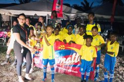 Champions At-Last-West Ruimveldt captain receiving the championship trophy from the Smalta Brand Representative in the presence of her team-mates, after defeating North Georgetown in the finale of the Girls Pee Wee Football Championship at the Ministry of Education ground, Carifesta Avenue